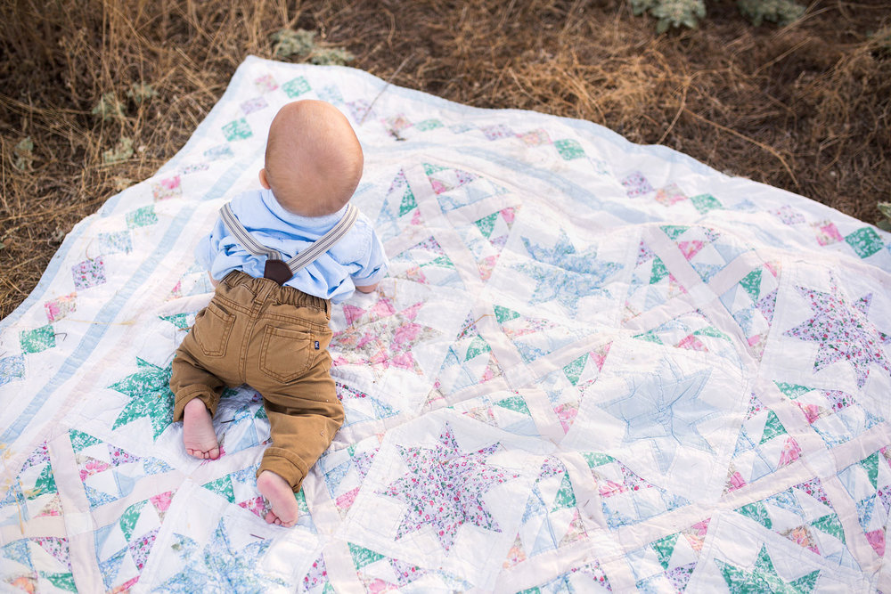 A One Year Old Baby Boy Wearing Suspenders On a Blanket, Amy Wright Photography, Roseville Photographer