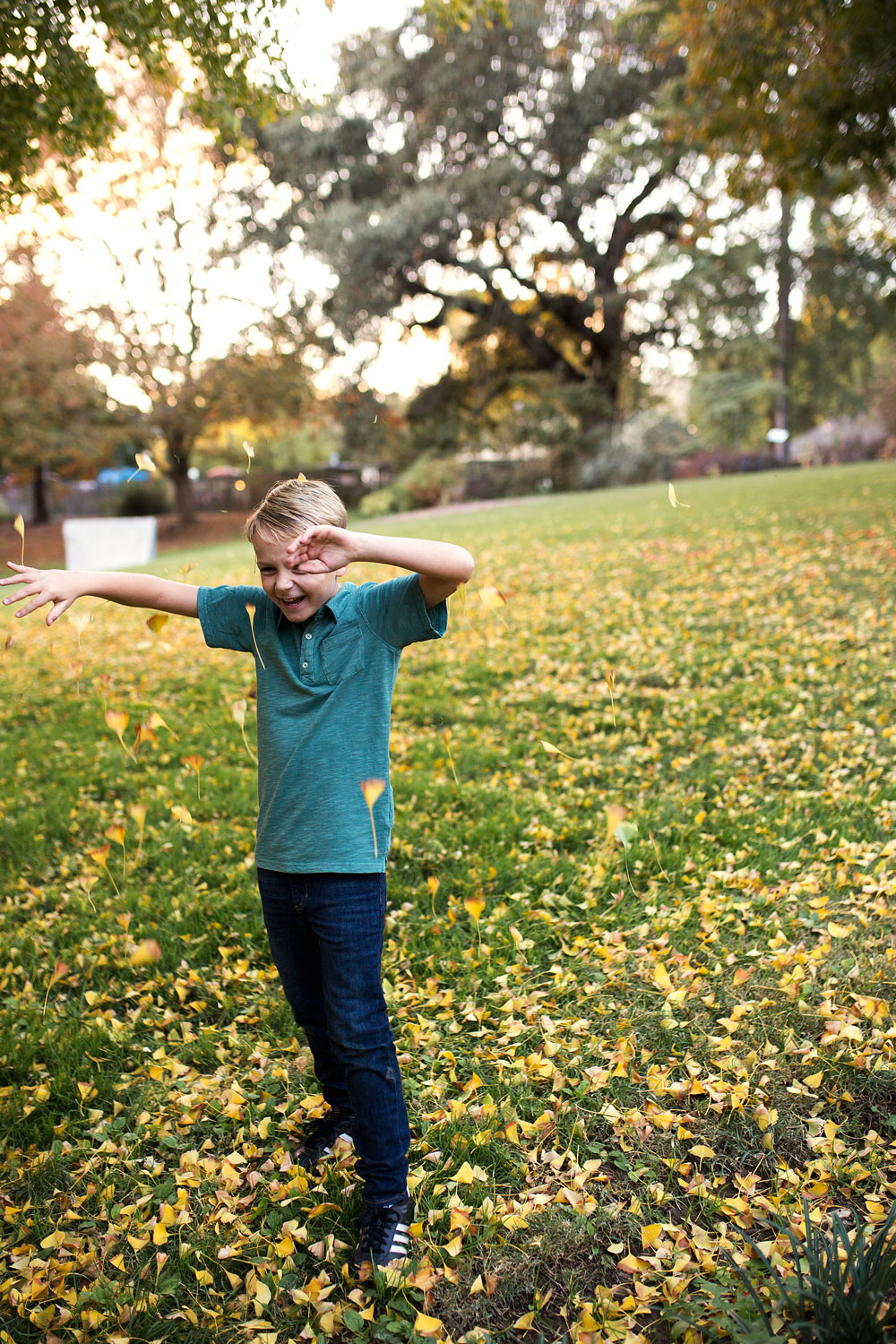 Boy playing in leaves at UC Davis Arboretum