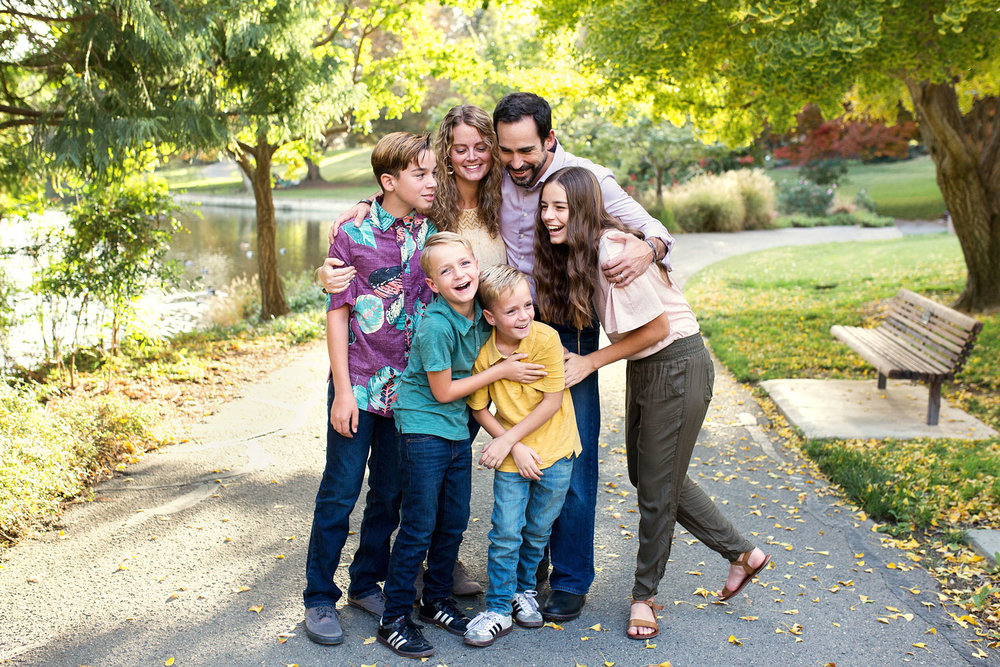 A family of six laughs together as they embrace and interact during a photo shoot in Sacramneto, California with Amy Wright Photography.