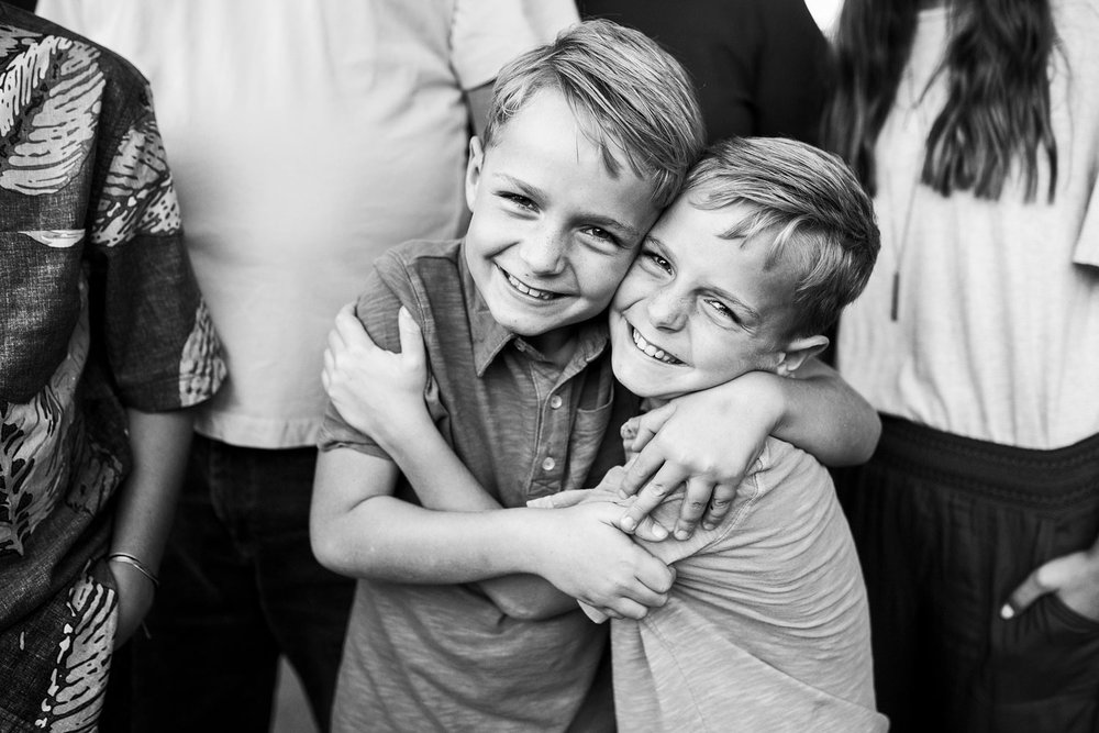Twins hug each other happily during a family photo session at the UC Davis Arboretum with Amy Wright Photography.