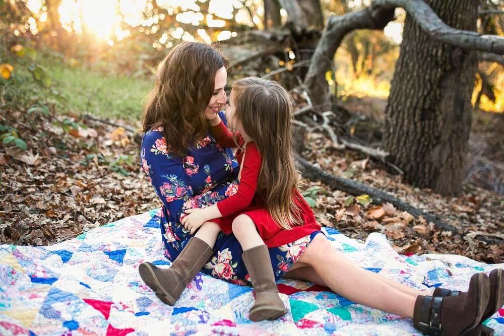 A mother and daughter sit and snuggle on a quilt during a photo session in Sacramento, California.