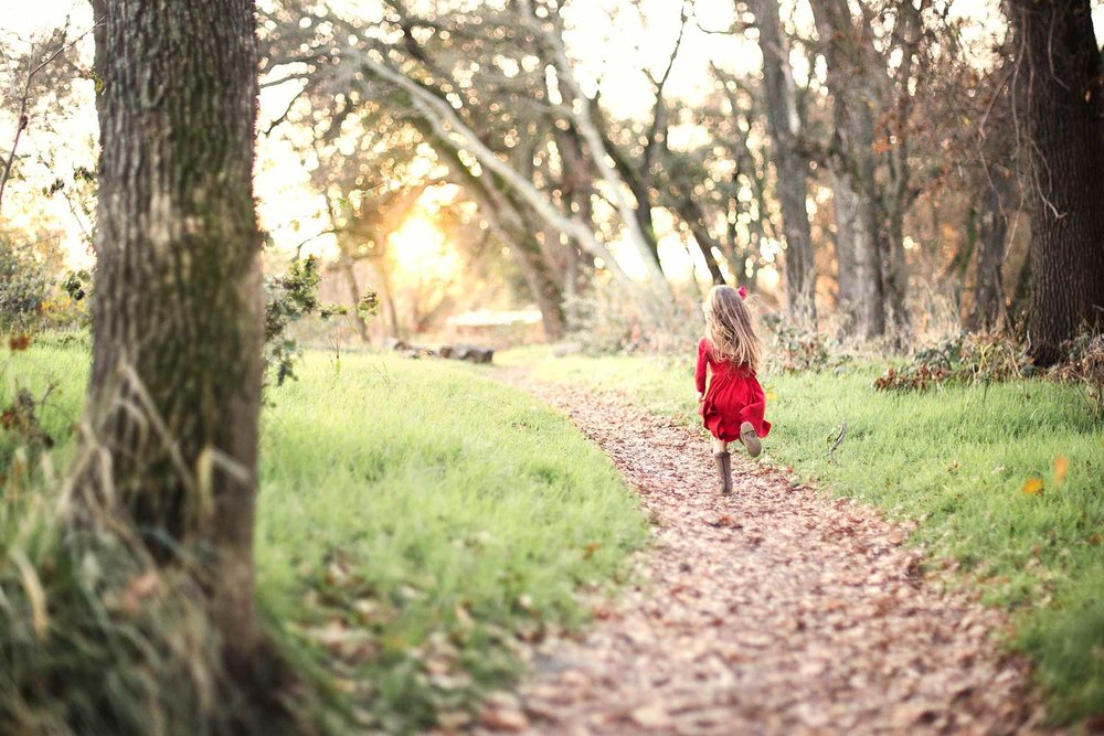 A girl runs on a path during a photo session in Roseville, California.