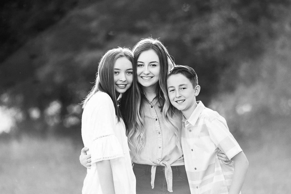 Two sisters and a brother smile for the camera and put their arms around each other in Roseville, California.