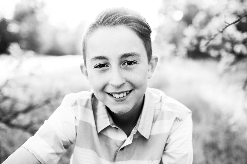 A pre-teen boy smiles for a picture during a family photo session with Amy Wright Photography in Roseville, California.