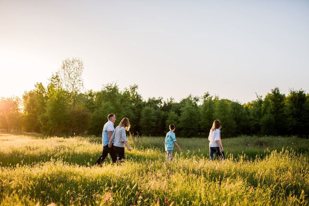 A family of five walks in beautiful evening light during a family photo session with Amy Wright Photography in Roseville, California.