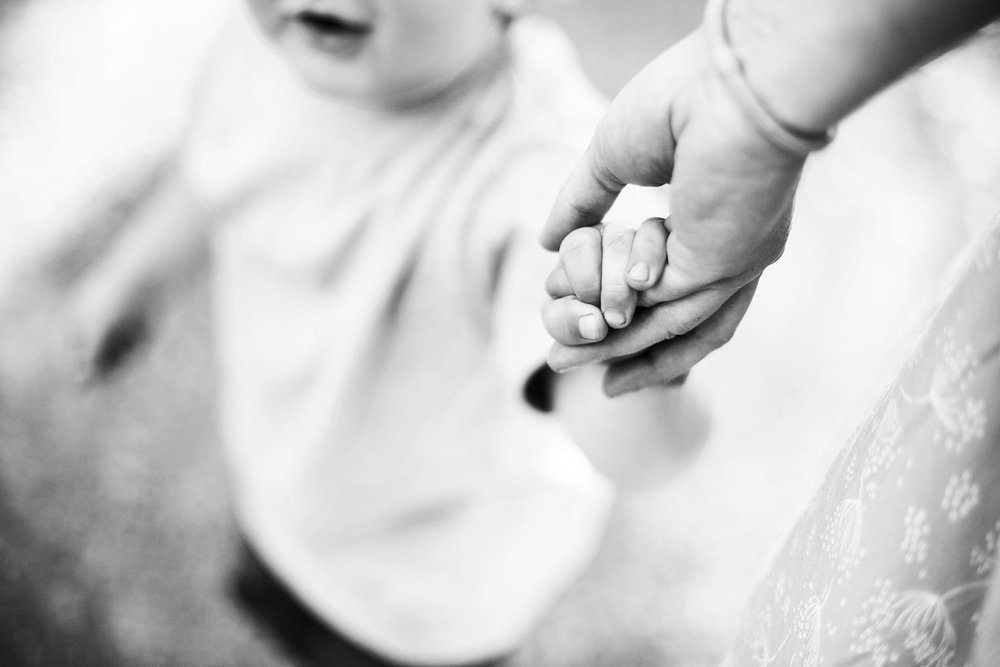 A boy holds his mother's hand during a family photo session with Amy Wright Photography in Sacramento County, California.
