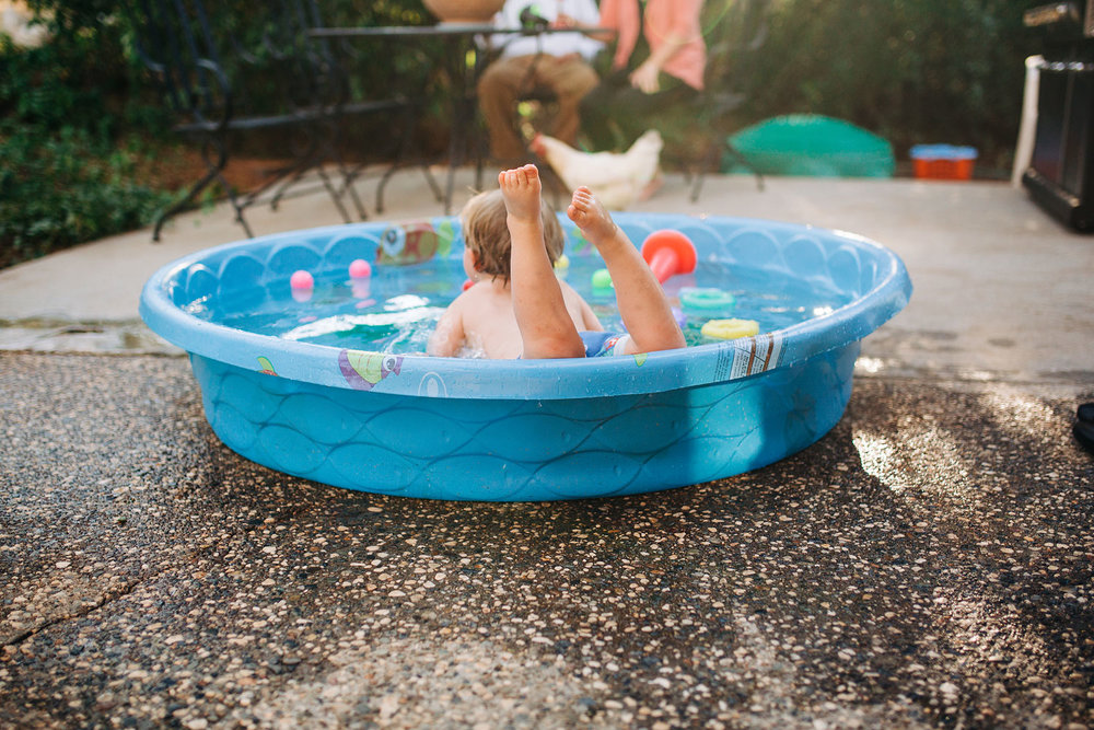 A boy swims in a kiddie pool in a backyard during an in-home lifestyle photo shoot in Northern California with Amy Wright Photography.
