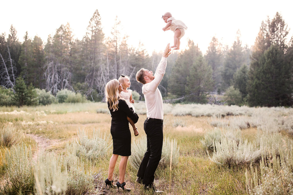 A family of four watches the baby being tossed up by Dad during a fun-filled family photo session with Amy Wright Photography based out of Roseville, California.