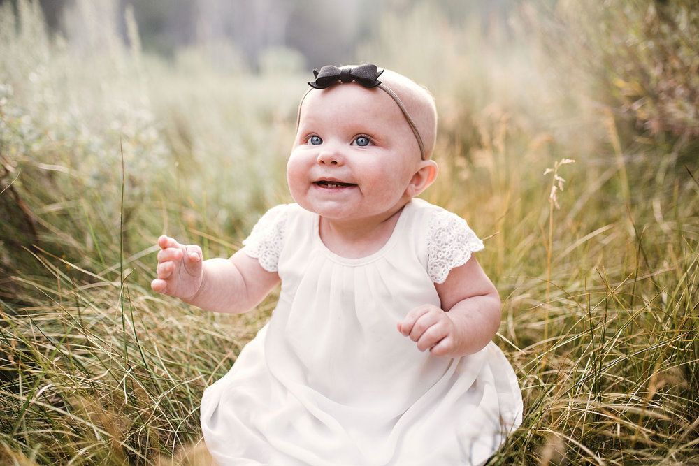 A baby sits in the grass during a family photo session with Amy Wright Photography based out of Sacramento, California.