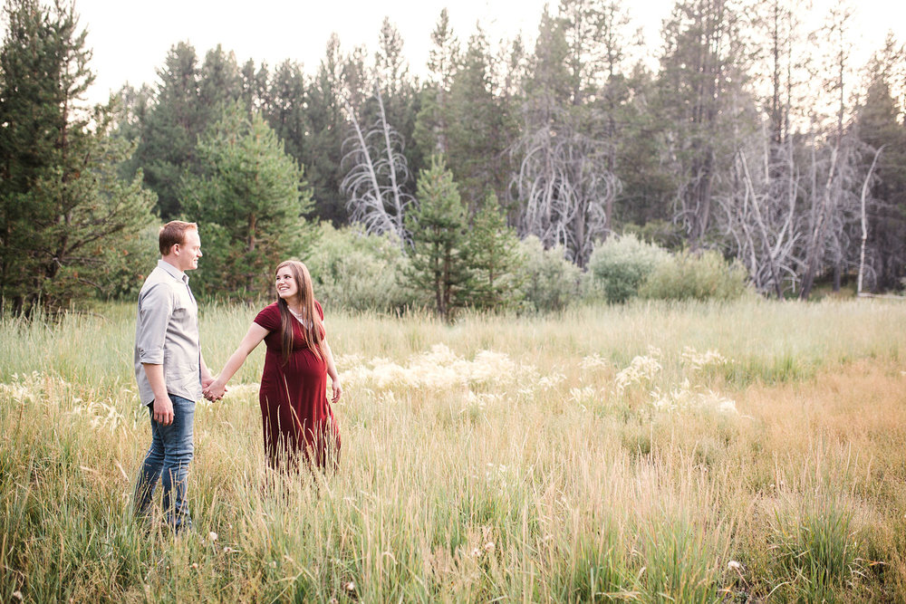 A pregnant wife and her husband walk together during a family photo session with Amy Wright Photography in Sacramento, California.