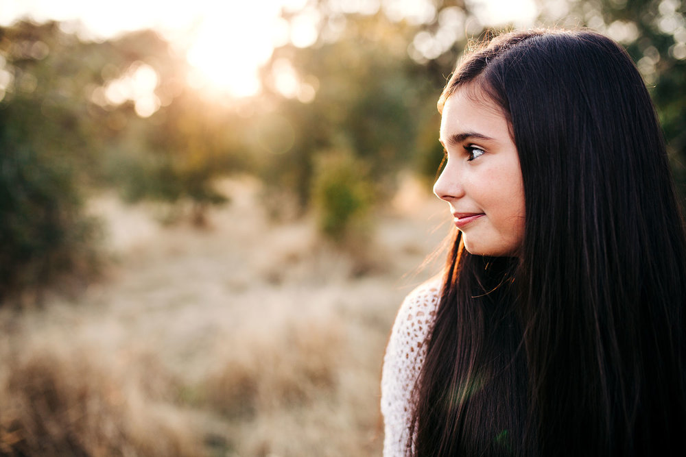 A girl looks to the side showing her profile during a family photo shoot with Amy Wright Photography in Roseville, California.