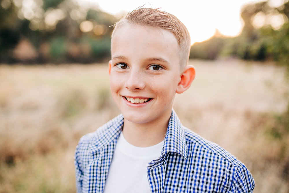 A boy is smiling for his portrait during a family photo session in Sacramento, California with Amy Wright Photography.