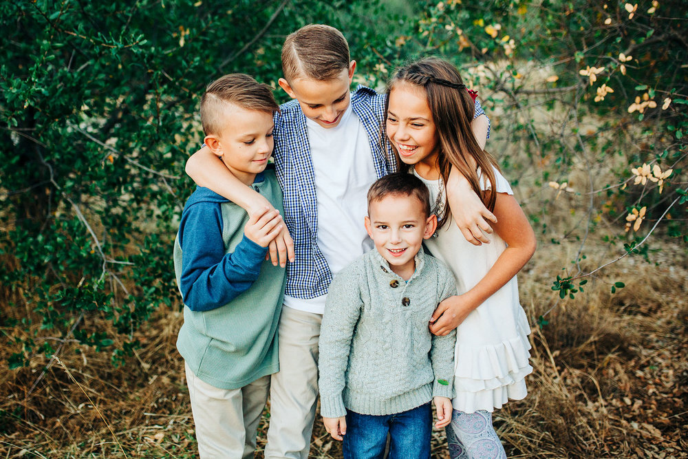 Four siblings wrap their arms around each other during a lifestyle photo session with Amy Wright Photography, based out of Sacramento, California.