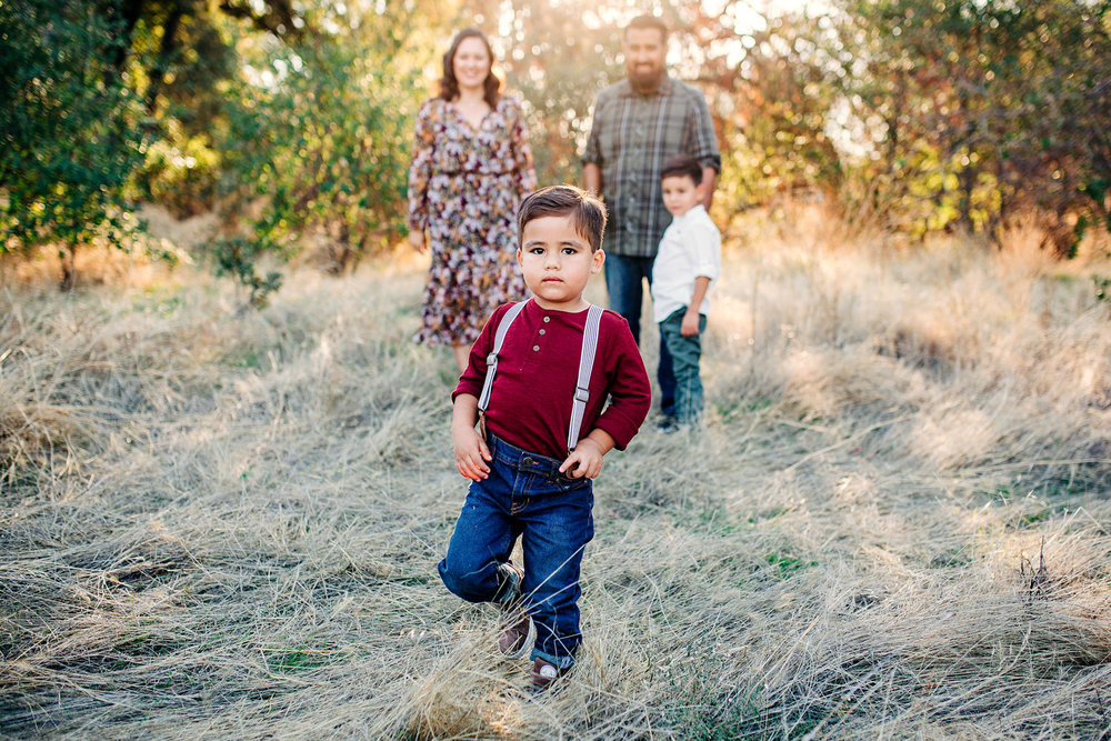 A boy in suspenders looks at the camera during a family photo session with Amy Wright Photography, based out of Roseville, California.