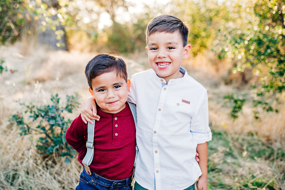 Two brothers put their arms around each other during a family photo session with Amy Wright Photography in Roseville, California.