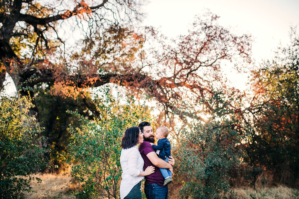 A family of three gets close during a family photo shoot with Amy Wright Photography based out of Roseville, Rocklin, and Sacramento, California.