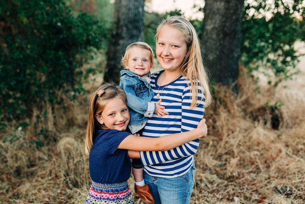 Three sisters hug happily during a family photo session with Amy Wright Photography in Roseville, California.