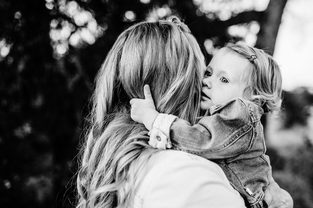 A baby girl hugs her mother during a photo mini session with her family in Rocklin, California with Amy Wright Photography.