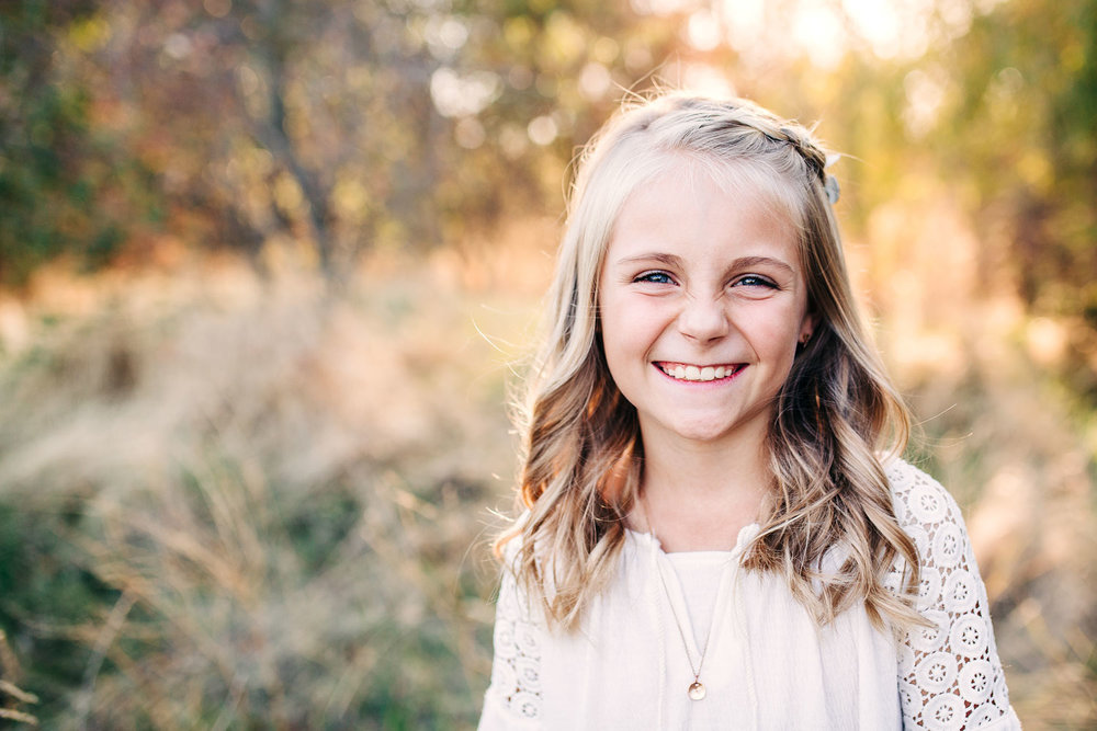 A girl smiles happily during family pictures with photographer Amy Wright who is based out of Sacramento, California.