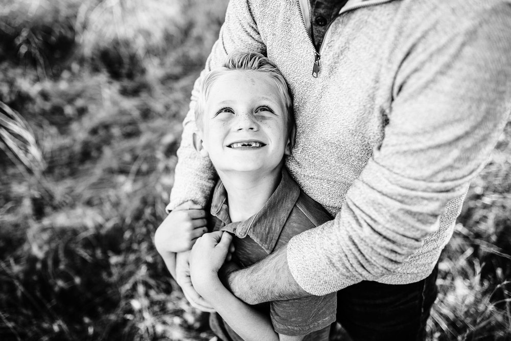 A son smiles up at his Dad with his arms around him during a lifestyle family photo session with Amy Wright Photography based out of Roseville, California.