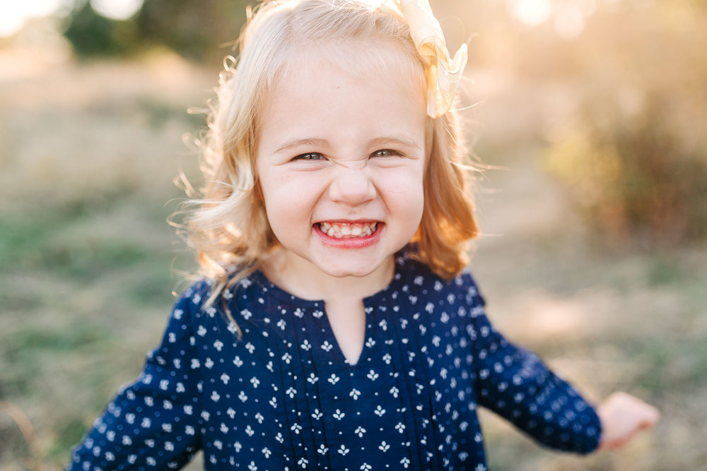 A toddler girl is giving a very happy grin during family photos in beautiful light with Amy Wright as their photographer in Roseville, California.