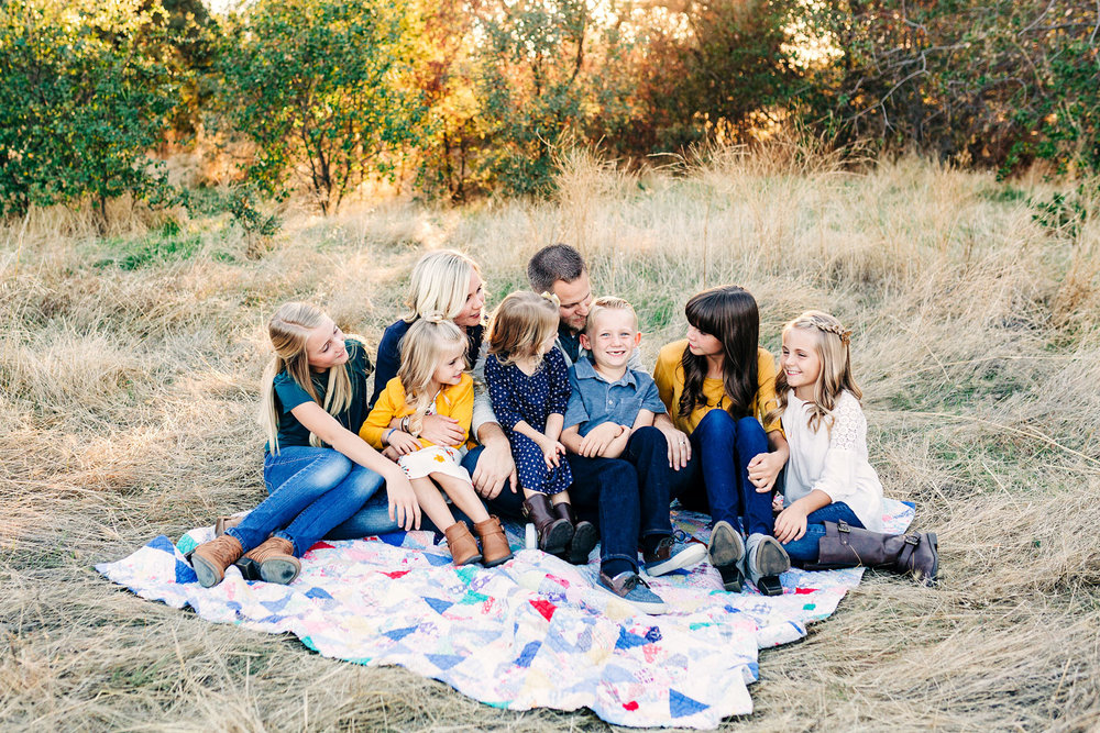 A family of eight sits on a quilt and enjoys each other's company during a lifestyle photo session outside in Roseville, California with Amy Wright Photography.