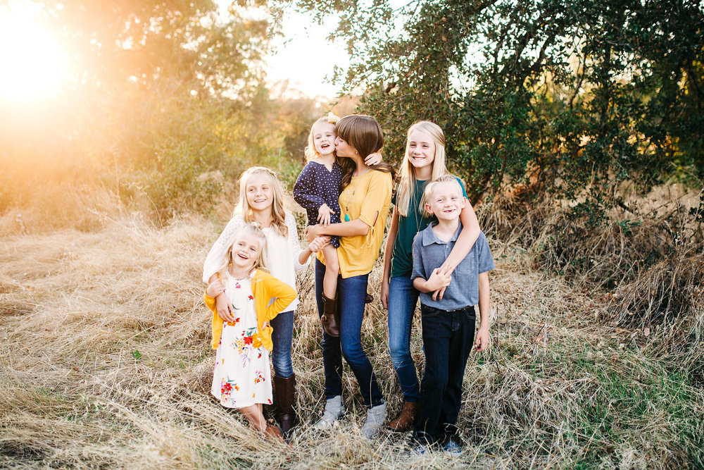 Six siblings put their arms around each other and have fun during a family photo session outside in Roseville, California.