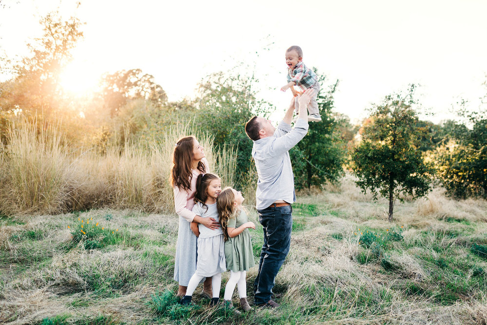 A dad tosses his baby in the air as his wife and two other children look on and smile during a family photo session in the Sacramento area of California.