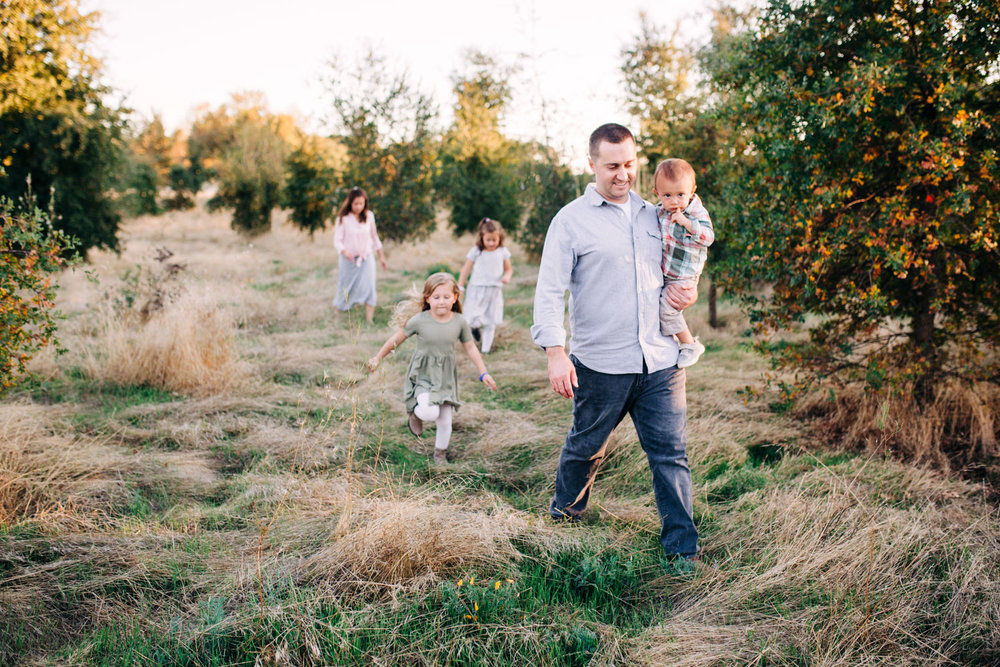 A family is walking in a field during a lifestyle photo session with their photographer, Amy Wright, who is based out of Roseville, California.