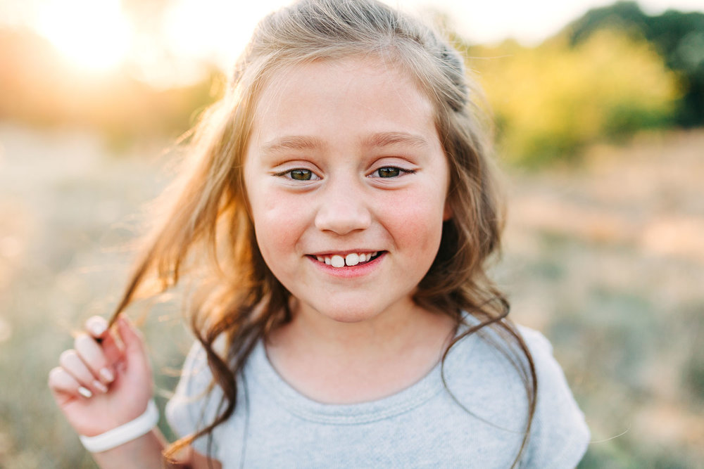 A girl sweetly looks into the camera as she plays with her hair during family pictures with Amy Wright Photography in Roseville, California.
