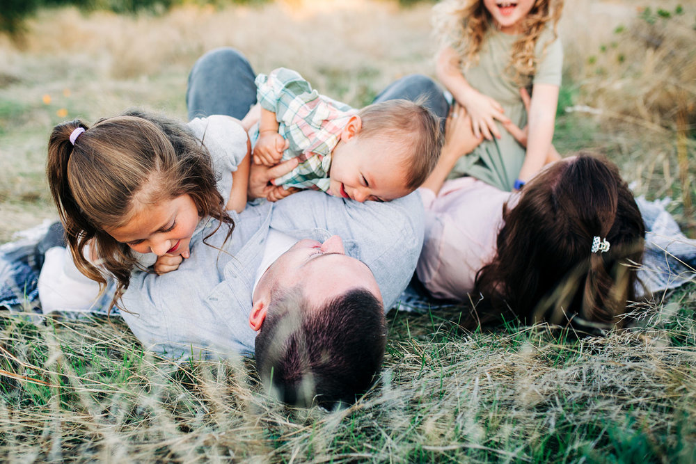 A family rolls around on the ground, laughing and playing together during family pictures with lifestyle photographer Amy Wright, based out of Sacramento, California.