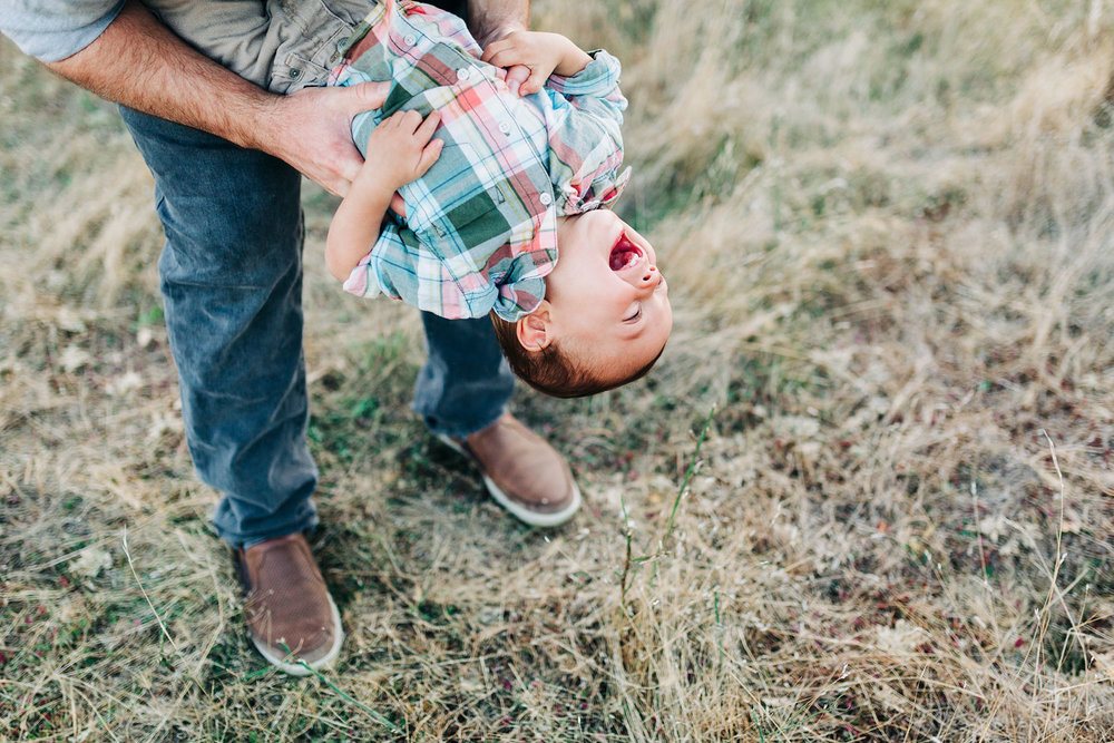 A one-year-old boy is dipped down with his dad as they play together during a family photo session in Roseville, California with Amy Wright as their photographer.