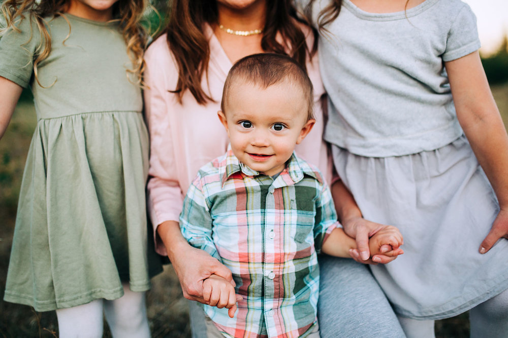 The baby of the family holds his mama's hands and gives a small grin for the picture during family portraits with Amy Wright Photography in Roseville, California.