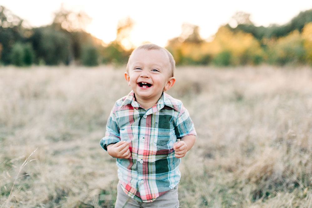 A one-year-old proudly shows off his skills standing up during a family photo session with Amy Wright Photography in Roseville, California.