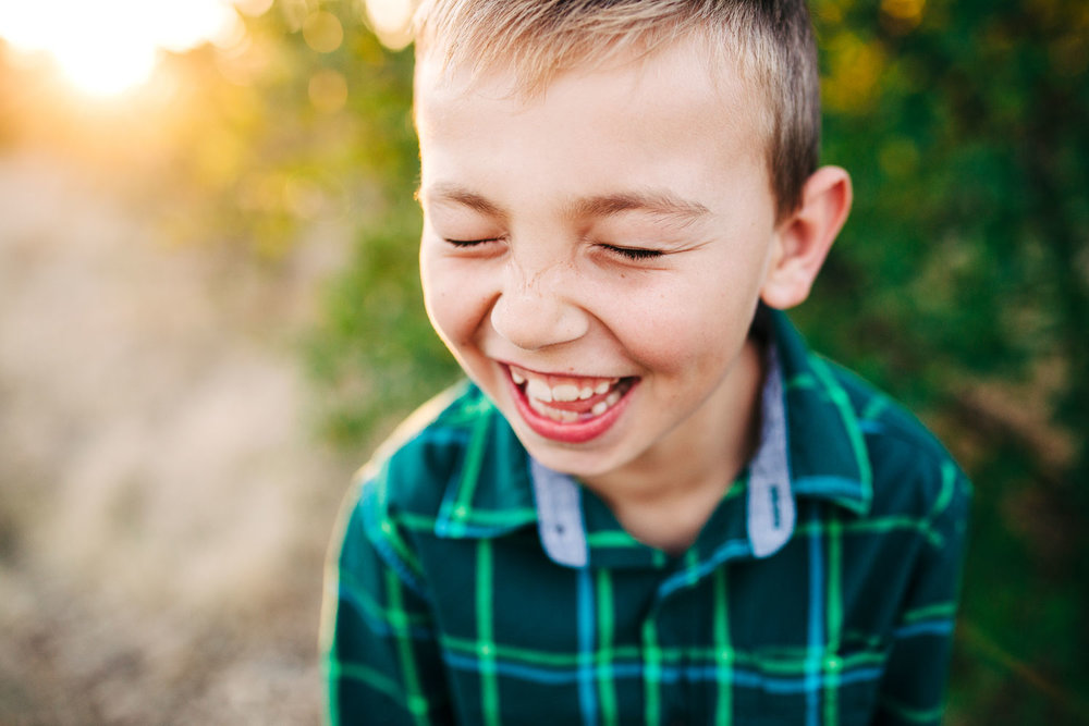 A boy is laughing during family pictures with Amy Wright Photography at a park in Roseville, California.