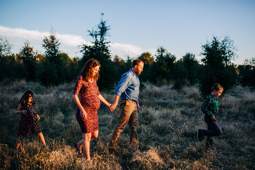 A family of four is walking toward the sunlight during a maternity photo session in a park in Roseville, California with Amy Wright Photography.