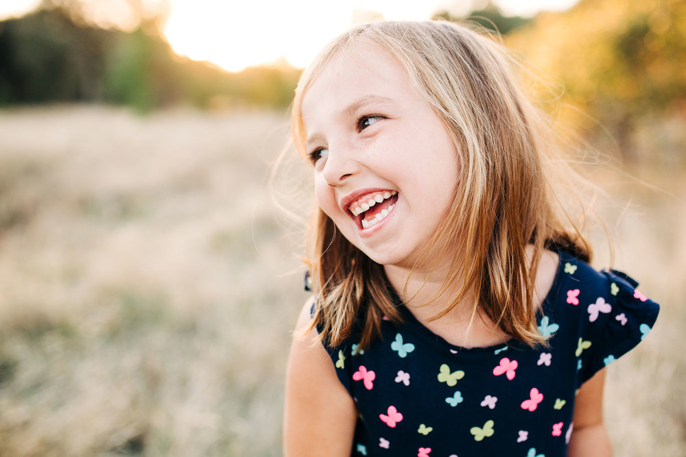 A girl is looking to the side and giggling for her picture during a family photo session with Amy Wright Photography, based out of Rocklin, California.
