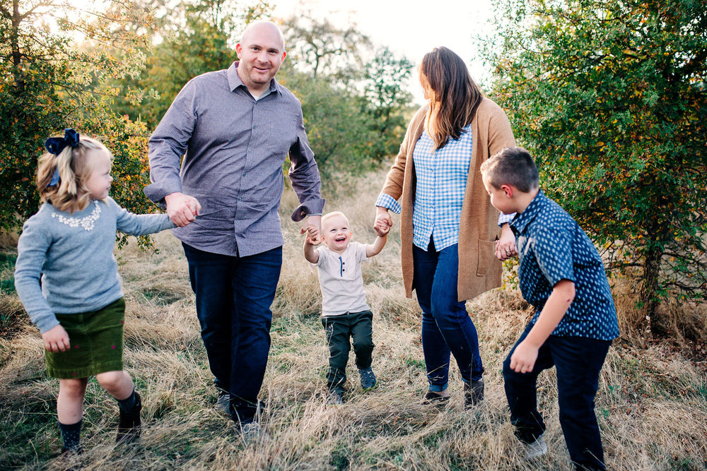 A family of five plays and laughs together during their photo session with Amy Wright Photography in Roseville, California.