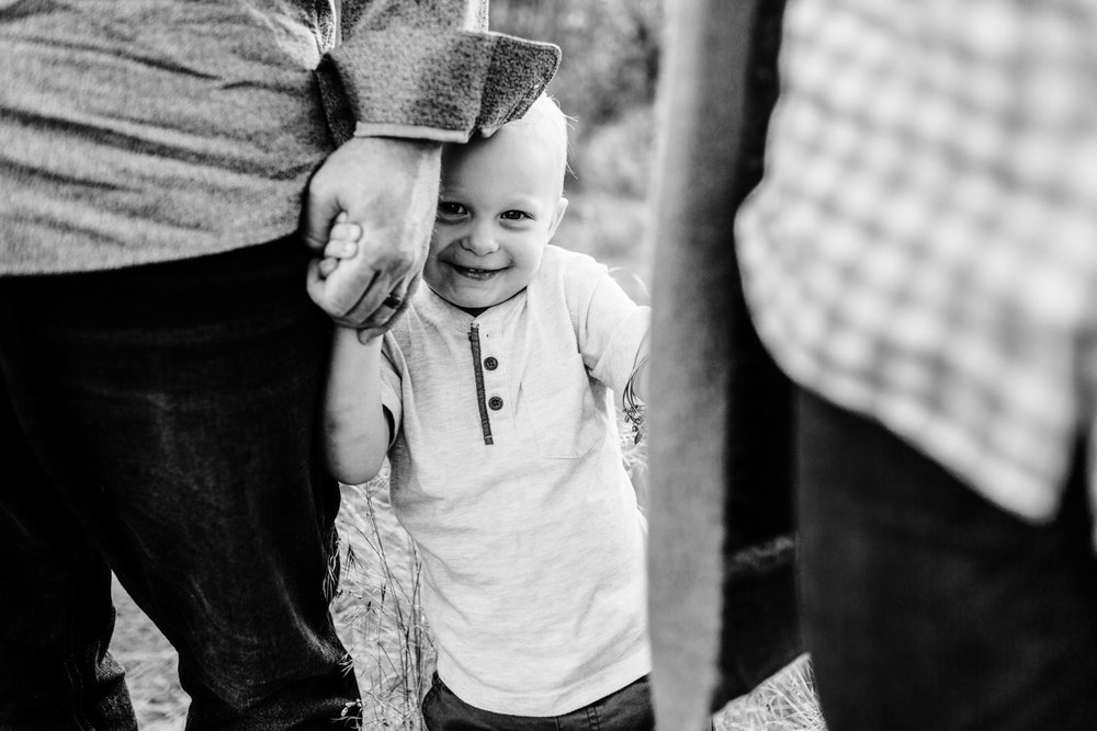 A toddler happily holds his father's hands and hides behind it playfully during a family photos session in Roseville, California.