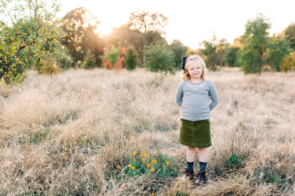 A girl stands in a field during golden hour for her portrait to be taken during family photo session with Amy Wright Photography in Roseville, California.