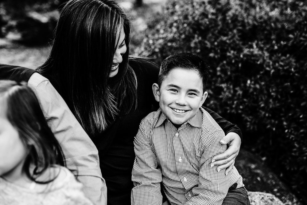 A mother puts her arm around her smiling son during family pictures with their photographer, Amy Wright, who is based out of Roseville, California.