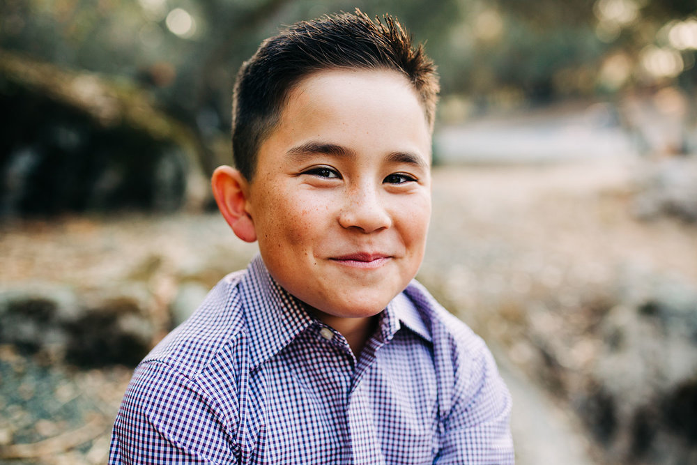 An elementary-aged boy smiles for his picture during a lifestyle family photo session with photographer Amy Wright in Roseville, California.