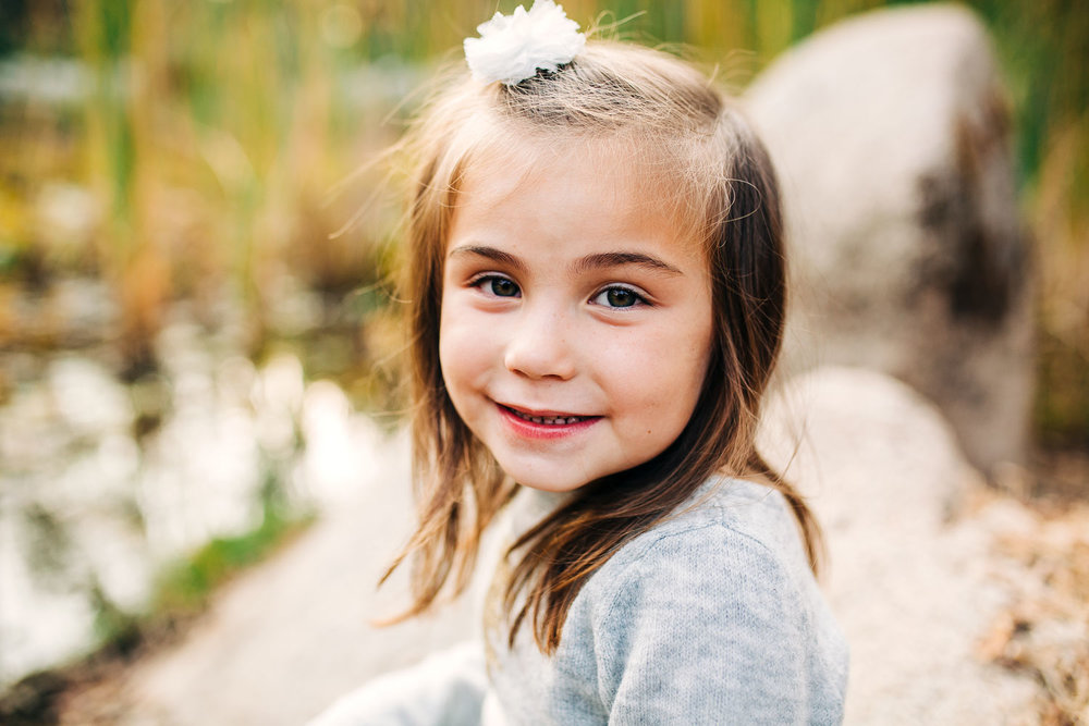A small girl looks at the camera for her portrait during a lifestyle home photo session with her family. Taken in Granite Bay, California.