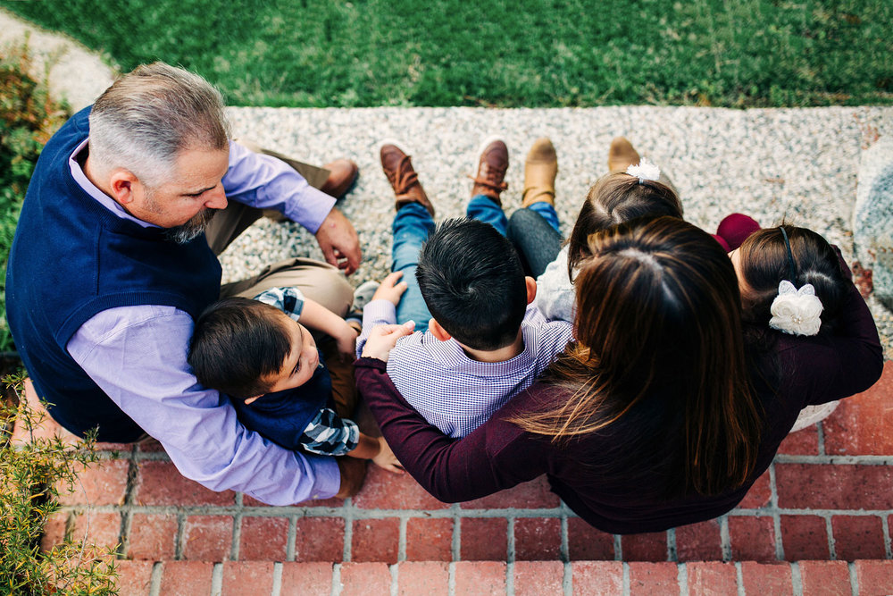 An overhead shot is taken of a family of six with their arms wrapped around each other during a photo shoot in Roseville, California.