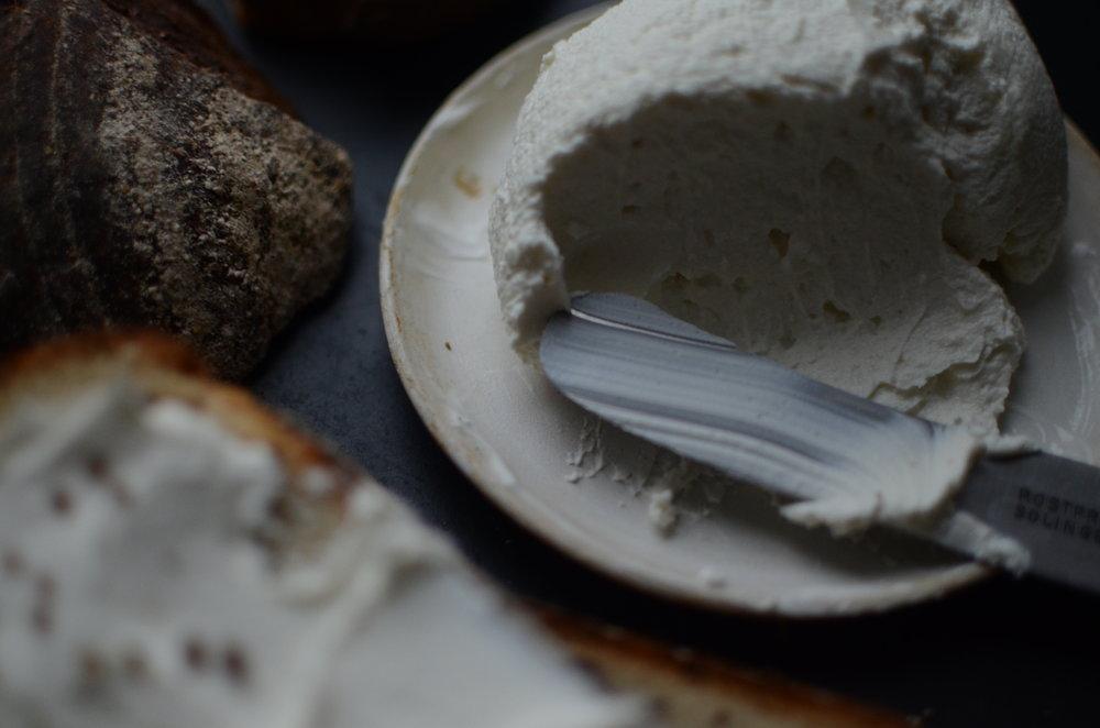"""Attēlā """"Baltais"""" eko govs piena jogurts notecināts 16h, tad tam pievienots """"Manas garšas"""" ozolkokā kūpinātais sāls un notecināts vēl 2h. Rezultātā iegūstot maigu krēmsieru ar nelielu kūpinājuma garšu."""