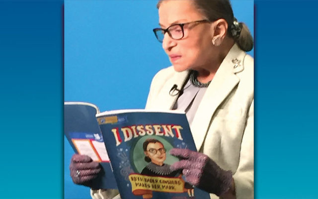 RBG reads  I Dissent . Image courtesy of the PJ Library and the Jewish Standard. https://jewishstandard.timesofisrael.com/notorious-rbg-concurs-with-dissent/
