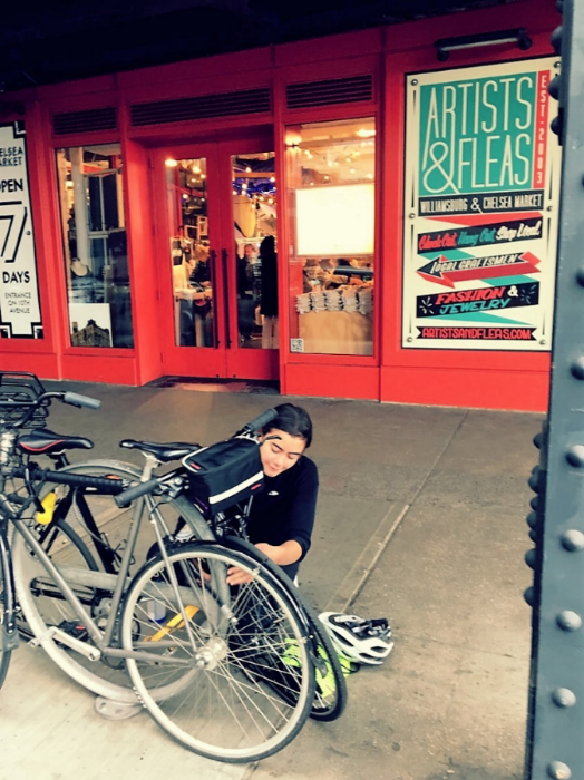 Yours truly having a very difficult time locking up her bike outside of the Chelsea Market
