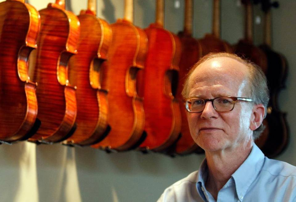 John Montgomery stands next to violins at his shop, John Montgomery Violins in Raleigh, NC on Monday, June 15, 2015. John Montgomery helped stop men who were trying to sell him stolen violins from Atlanta, Georgia.