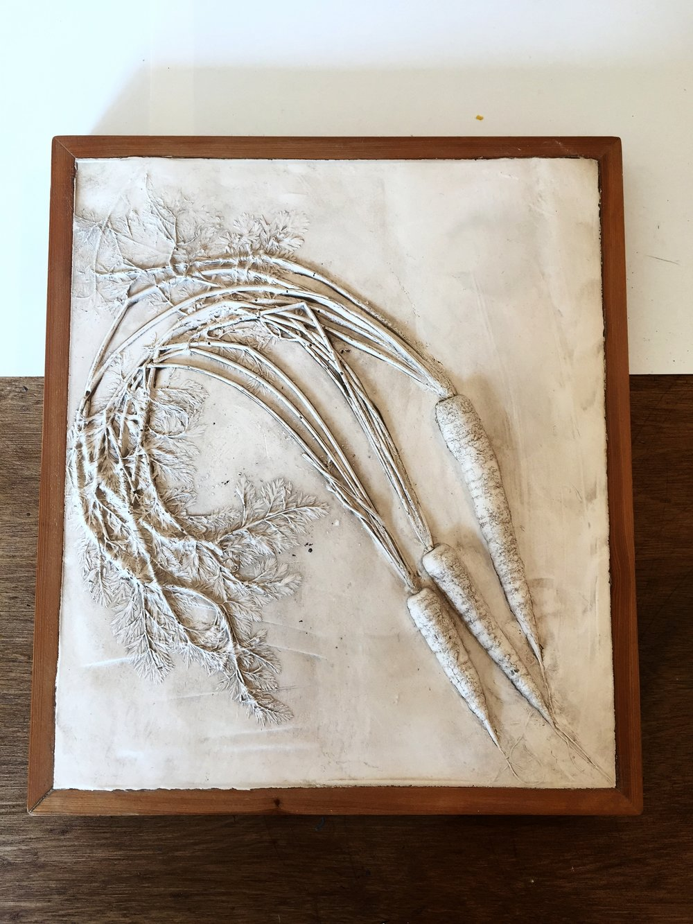 A fully framed cast carrot wall-hanging