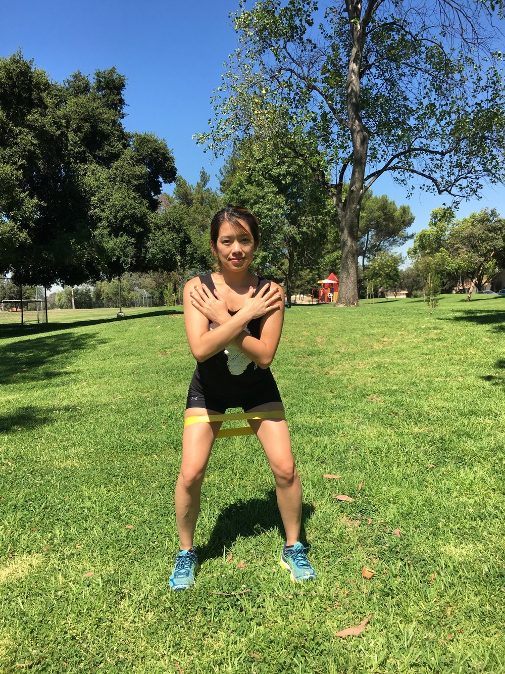 Step 1: Starting position front view. Feet spread apart outside hip width and knees aligned with ankles.